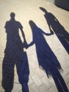 Shadows of parents and a child depict the challenges and benefits of co-parenting.