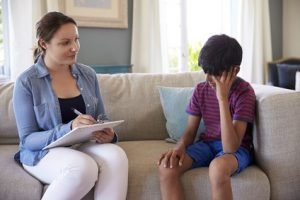 Young Boy With Problems Talking With Counselor