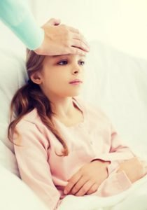 Young girl in bed with mothers hand on her forehead